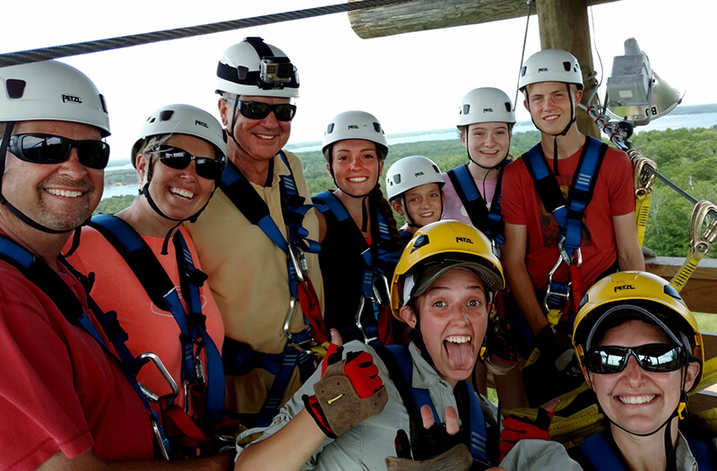 Group smiles during zipline tour on brainerd course